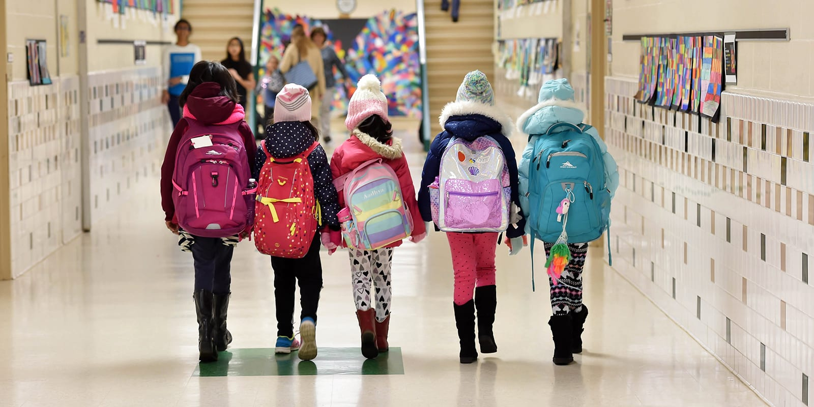 girls from rear with backpacks