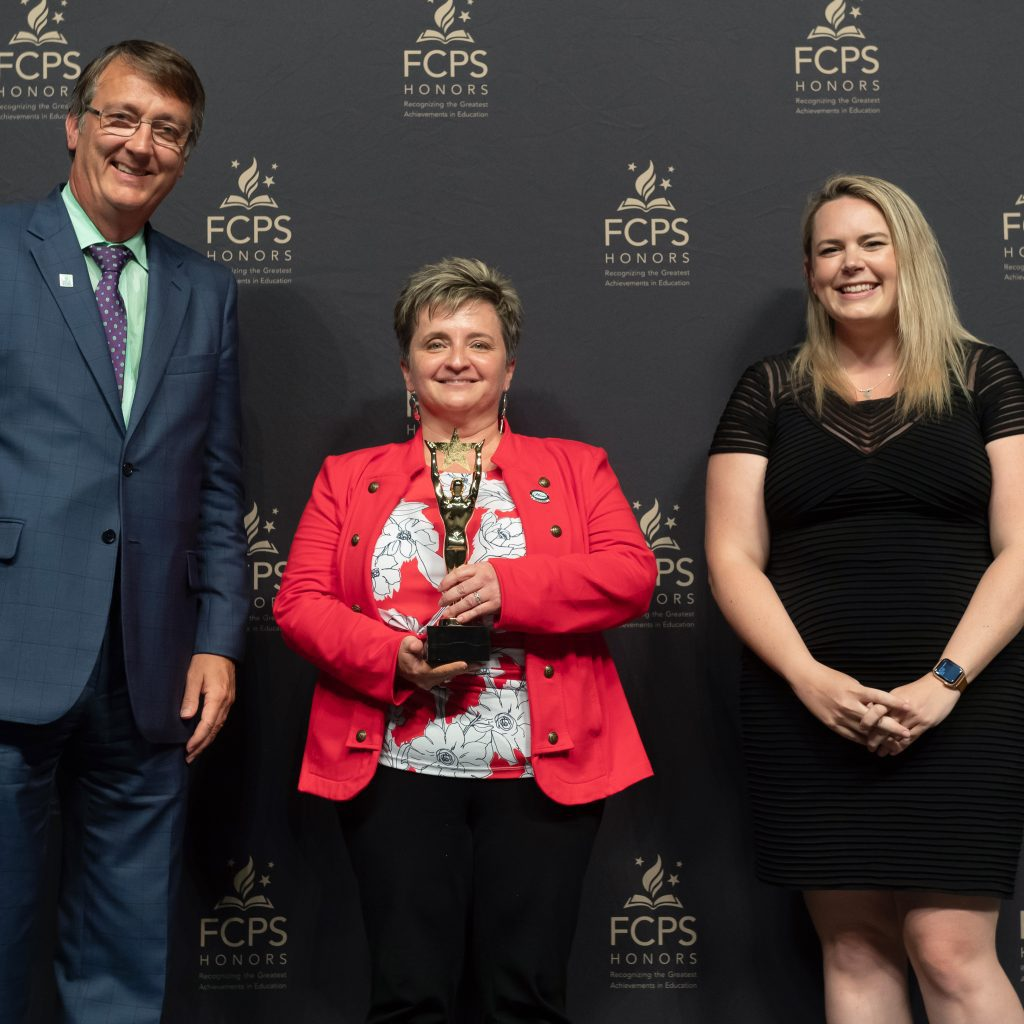 The second Outstanding Nonschool-based Leader Tracey Jewell receives the Eddy from Dr. Brabrand and Bridget Werkheiser of Milestone Towers