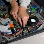 Photo of hands working on computer motherboard